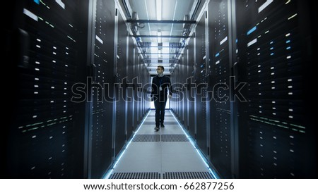 Shot of IT Engineer Walking Through Data Center Corridor with Rows of Rack Servers. #662877256