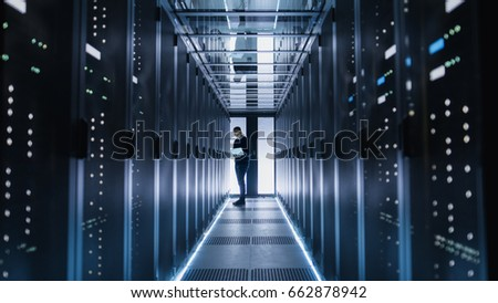 Male IT Engineer Works on a Laptop in a Big Data Center. Rows of Rack Servers are Seen. #662878942
