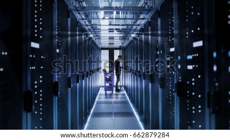 IT Engineer With Crash Cart Puts Hard Drives into Open Rack Server Cabinet. He's Working in Big Data Center. #662879284