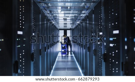 IT Engineer With Crash Cart Puts Hard Drives into Open Rack Server Cabinet. He's Working in Big Data Center. #662879293