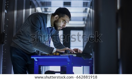 IT Engineer with Tool Cart Working on a Laptop Computer, he Deploys new software. He Stands at a Corridor of a Large Data Center Full of Rack Servers. #662881918