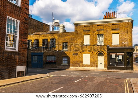 Typical old English buildings, low brick buildings across a narrow street, interesting old London architecture, english houses #662907205