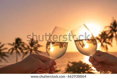 Cheers with wine glasses in a beautiful sunset beach setting.  #662938864