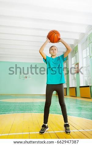 Active preteen girl tossing basketball in rim #662947387