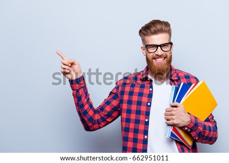 Smiling young nerdy red bearded stylish student is standing with books on pure background in glasses and casual bright outfit, pointing on the copyspace