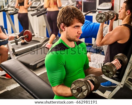 Friends in gym workout with fitness equipment. Man do dumbbell exercise at sport room. Group people working on simulator his body and running on treadmill on background. Demonstration of power. #662981191