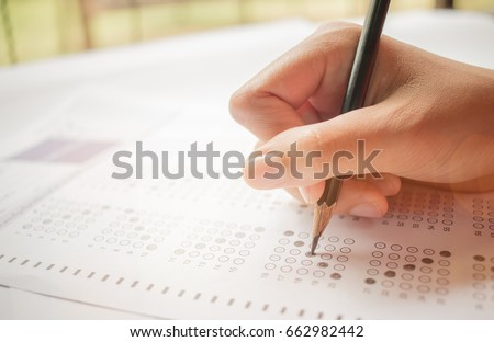 hand student testing in exercise and taking fill in exam carbon paper computer sheet with pencil at school test room, education concept