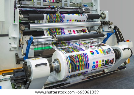 Large offset printing press or magazine running a long roll off paper in production line of industrial printer machine. Royalty-Free Stock Photo #663061039