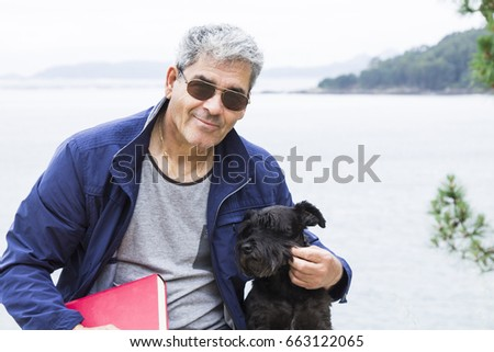 Senior man with book and dog sitting with seascape #663122065