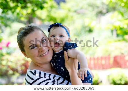Cute little baby girl with mother on summer day in garden. Happy woman holding smiling child on arm. Kissing, hugging. #663283363