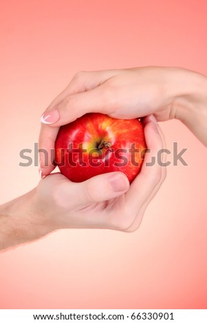 Apple between man and woman hand on red background #66330901