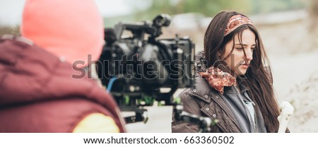 Behind the scene. Actress in front of the camera on the film set outdoor location. Group movie scene Royalty-Free Stock Photo #663360502