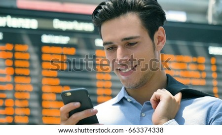 A young handsome businessman (student) in a shirt, working on the phone, in the background of a schedule of trains, buses, planes, ferries, holds a jacket. Concept: new business, travel, communication #663374338