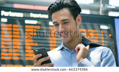 A young handsome businessman (student) in a shirt, working on the phone, in the background of a schedule of trains, buses, planes, ferries, holds a jacket. Concept: new business, travel, communication #663374386