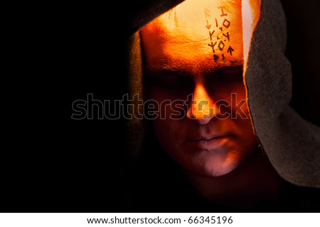 Mystery monk with the runes on the face. Portrait in the shadows. #66345196