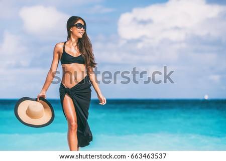 Luxury travel beach vacation elegant swimwear bikini woman with sunglasses, sun hat, black pareo. Body skin care lifestyle. #663463537
