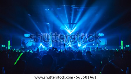 Silhouette in night club under blue rays beam and young people holding light saber enjoying at concert concept. Royalty-Free Stock Photo #663581461