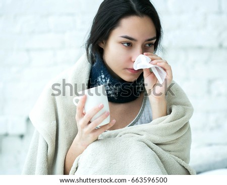 Young woman sick in bed with temperature drinks hot. Indoor shot. #663596500