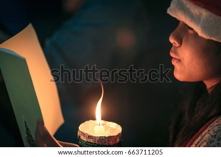 A children singer of caroler hands holding candle and book with singing carol song on celebration of Christmas day background