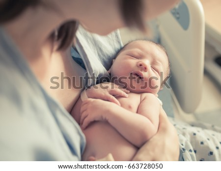 New born baby boy resting in mothers arms.  Royalty-Free Stock Photo #663728050