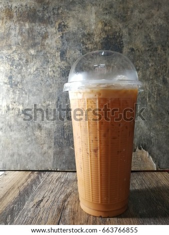 Cold tea in plastic glass on wooden background #663766855