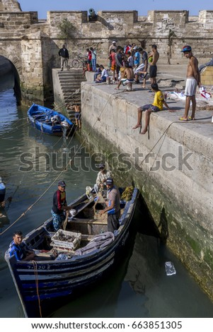 ESSAOUIRA, MOROCCO - AUGUST 01, 2013 : Fishermen return to the harbour within the old fortress walls at Essaouira. The present city of Essaouira was built during the 18th century. #663851305