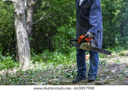 Man holding mechanical power-driven cutting tool (chainsaw)  #663897988