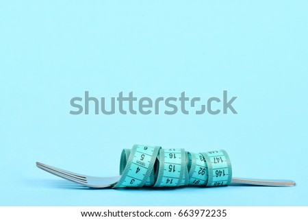 Fork wrapped around with tape for measuring isolated on light blue background with copy space. Concept of diet and healthy nutrition #663972235