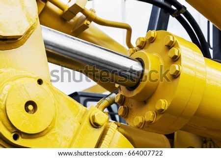 hydraulics tractor yellow. focus on the hydraulic pipes Royalty-Free Stock Photo #664007722