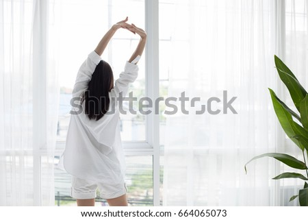 Asian woman waking up in her bed fully rested and open the curtains in the morning to get fresh air.
