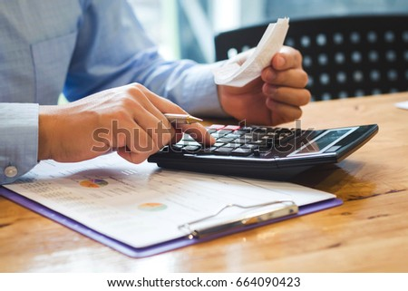 People use a calculator and calculate office expenses Royalty-Free Stock Photo #664090423