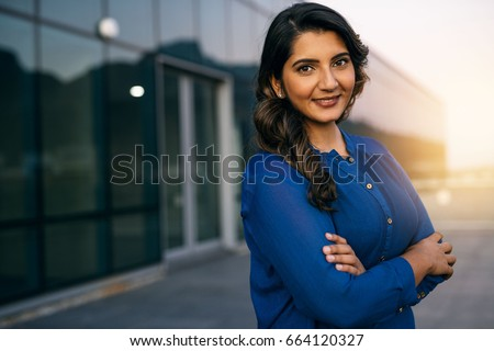 Portrait of a confident young Indian businesswoman standing with her arms crossed outside on an office building balcony overlooking the city at dusk #664120327