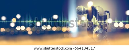 Microphone and headphones.Live music and blurred stage lights. Music background Royalty-Free Stock Photo #664134517