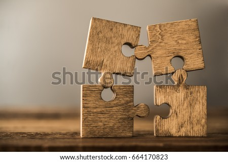 4 Four brown pieces of puzzle stand on wooden table isolated on gray or white background. empty copy space for inscription or objects. idea, sign, symbol, concept of connecting #664170823