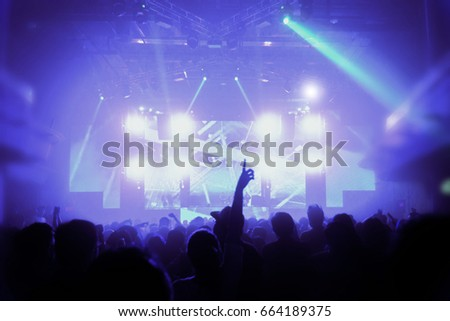 Silhouette hands of audience crowd people use smart phones enjoying the club party with concert. Celebrate new year party , Blurry night club DJ party people enjoy of music dancing sound . #664189375