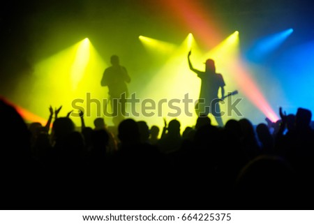 Guitarist and singer on the stage highlighted with colorful spotlights and crowd of fans in the foreground, defocused image #664225375