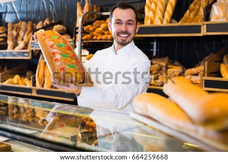Young guy seller is offering fresh festive cake in bakery.  #664259668