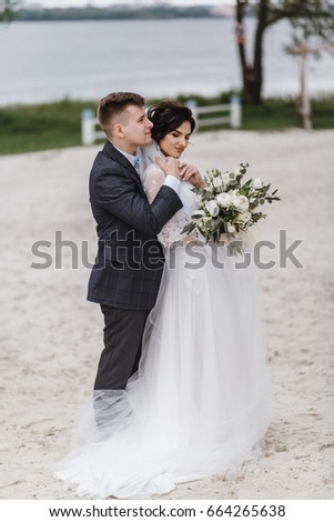 Beautiful newlyweds walking along the sand on the beach. Loving and affectionate. Hold each other's hands, hug and kiss #664265638
