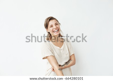 Cheerful happy young beautiful girl looking at camera smiling laughing over white background. Royalty-Free Stock Photo #664280101