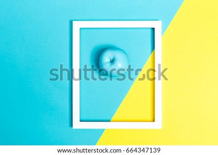 Painted blue apple on a bright split color background