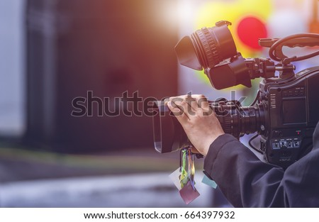 Video camera operator working with his equipment Royalty-Free Stock Photo #664397932