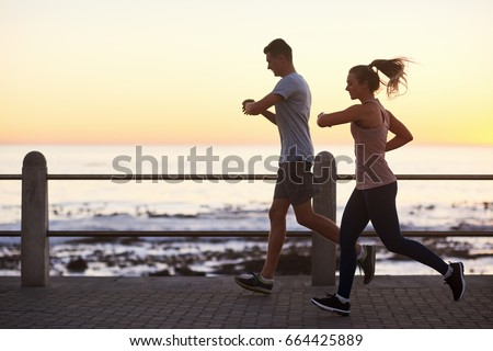 Couple looking at their fitness tracking app while running along the ocean at sunset, fit active lifestyle #664425889