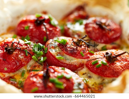 Oven baked tomatoes stuffed with spinach, cheese and herbs, close up. Delicious and nutritious vegetarian meal #664465021