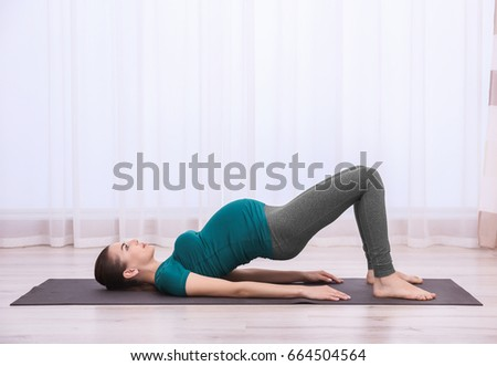 Beautiful pregnant woman doing exercise indoors #664504564