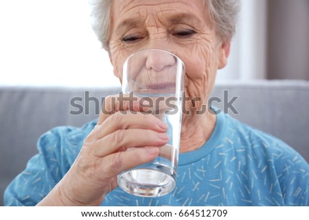 Elderly woman drinking water at home. Concept of retirement #664512709