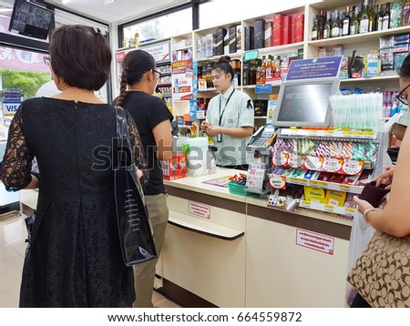 CHIANG RAI, THAILAND - JUNE 1 : Unidentified people waiting to pay  at the cashier counter at a 7-Eleven shop on June 1, 2017 in Chiang rai, Thailand. #664559872