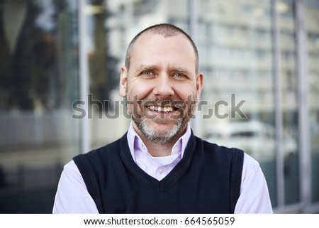 Portrait of smilingl businessman is standing in front of the building. #664565059