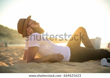 Handsome guy chilling at the beach #664625623