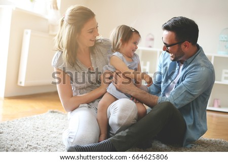 Happy family sitting on floor with their little baby. Family spending time at home with their daughter. #664625806