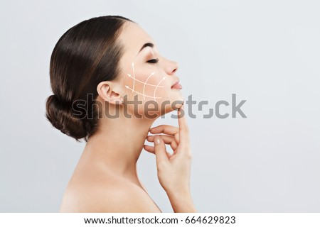 Profile of young female with clean fresh skin, antiaging concept. Girl touching face with closed eyes, lifting arrows showing facial anti-aging treatment on skin #664629823